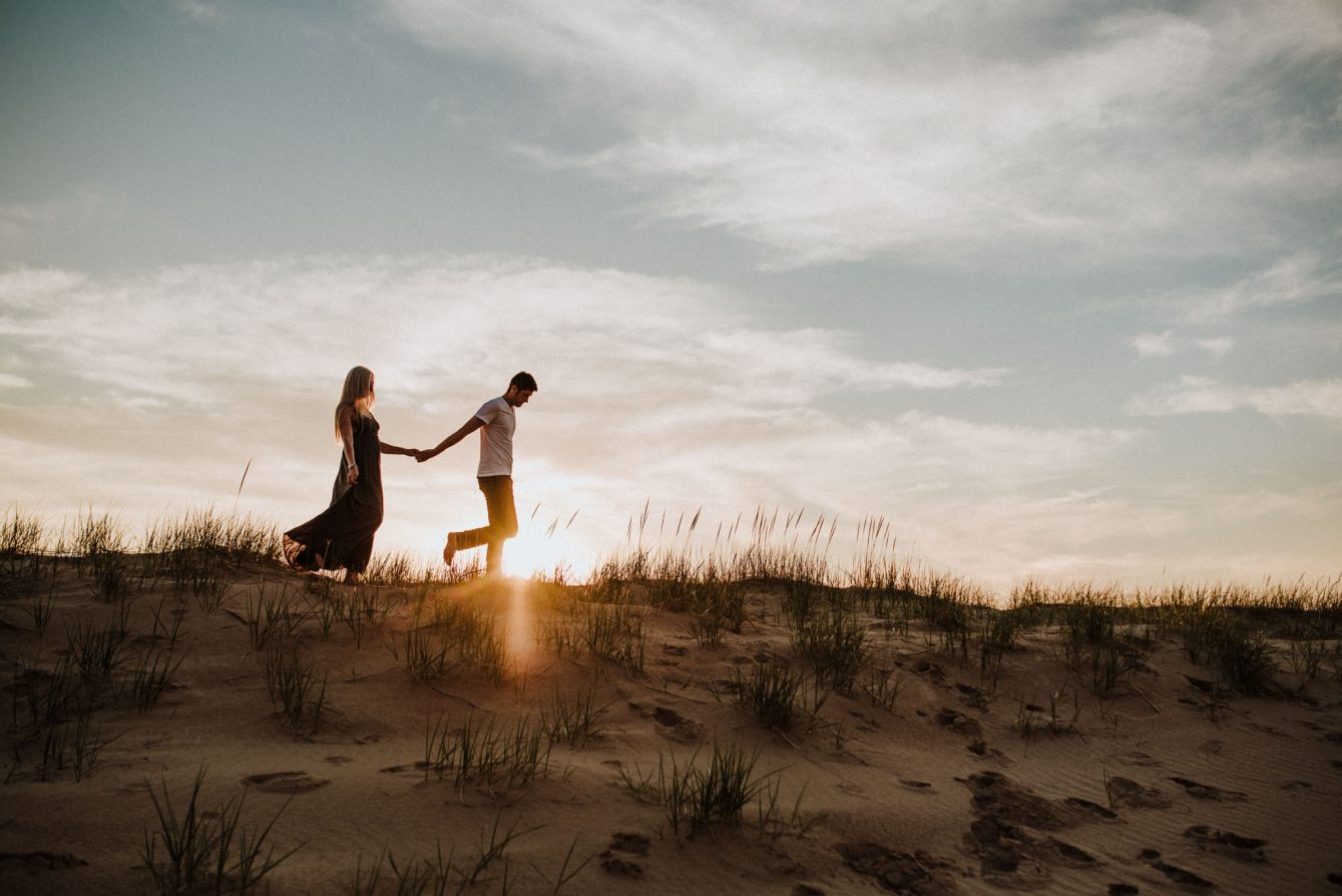 couple holding hands walking across a dune at sunset