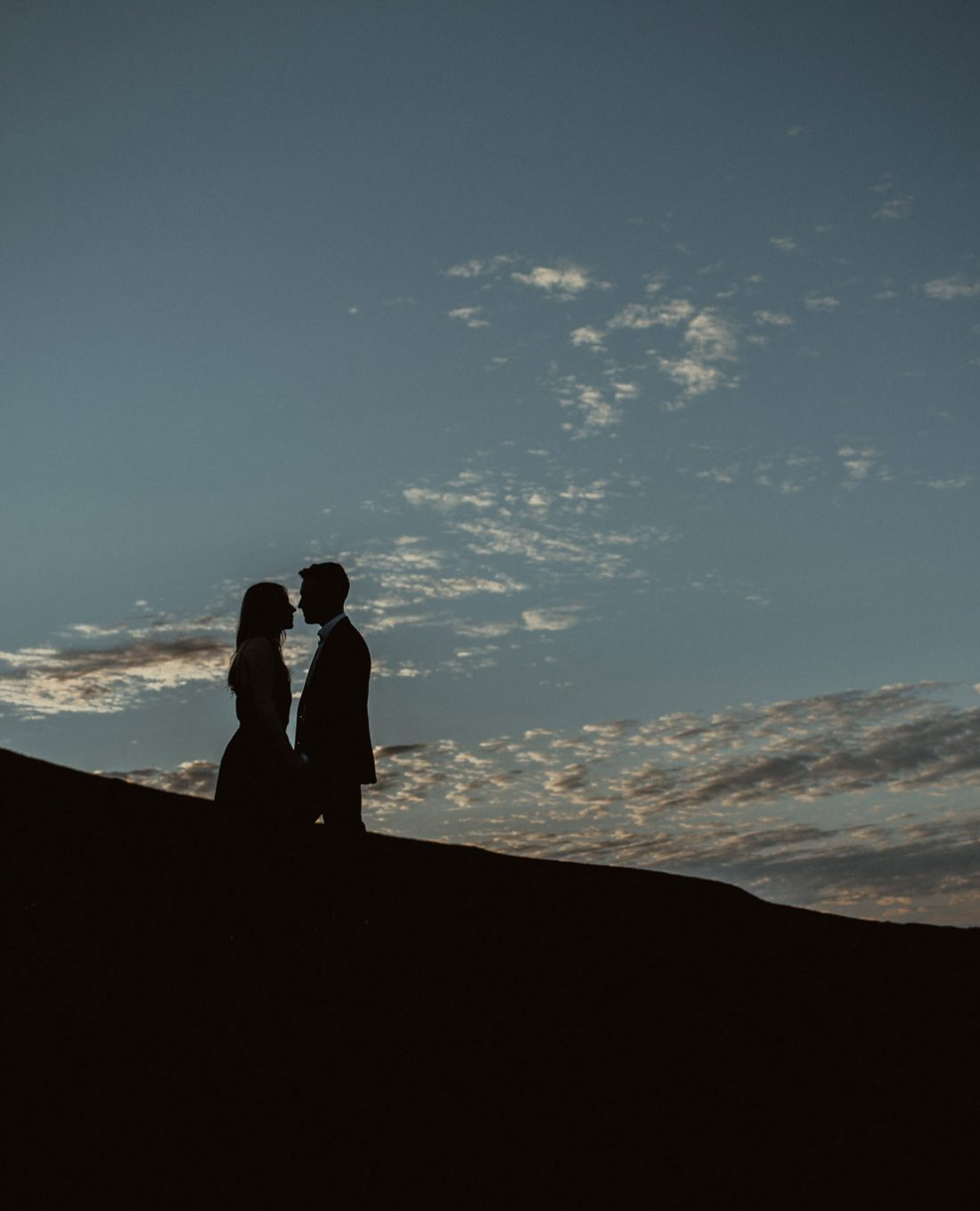 Couple silhouetted by the sky in Scotland