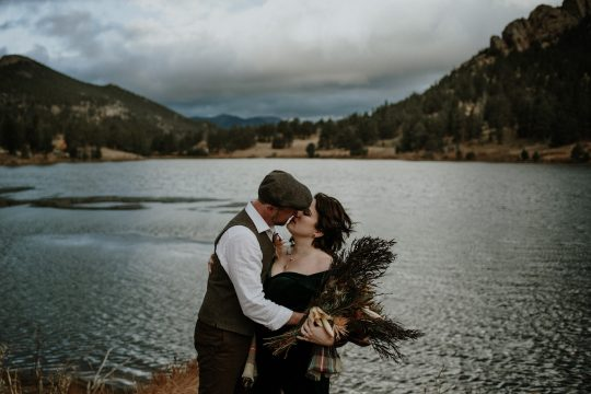 Elopement couple wearing plaid and feathers kissing at Lily Lake in Colorado.