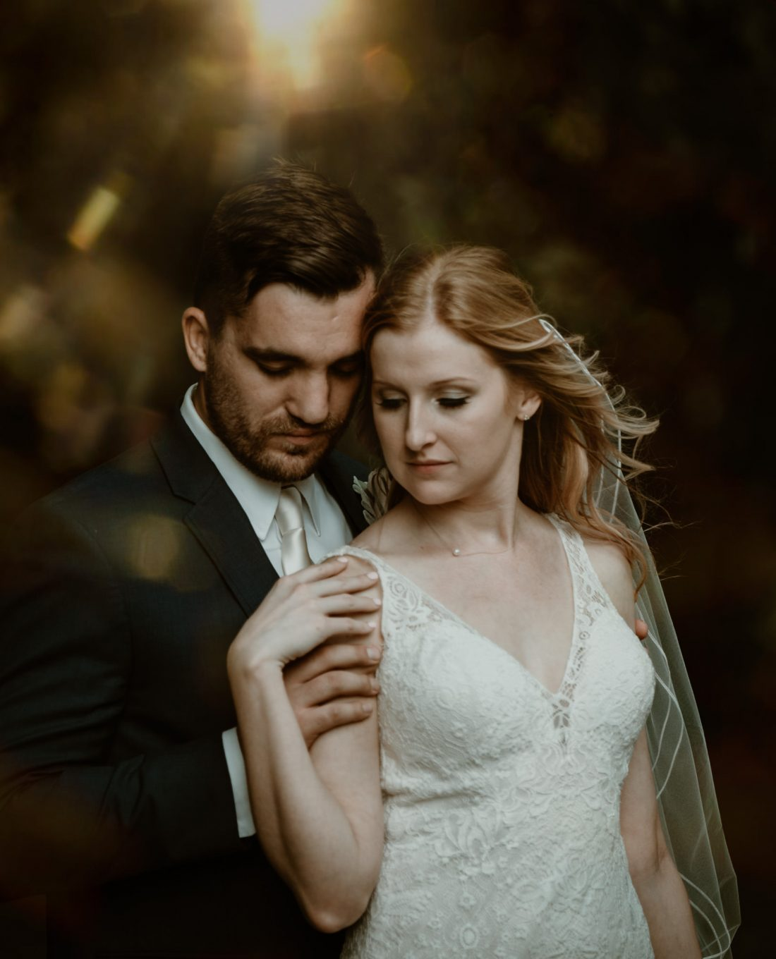 A bride and groom standing together in an intimate pose, with magical light surrounding them.
