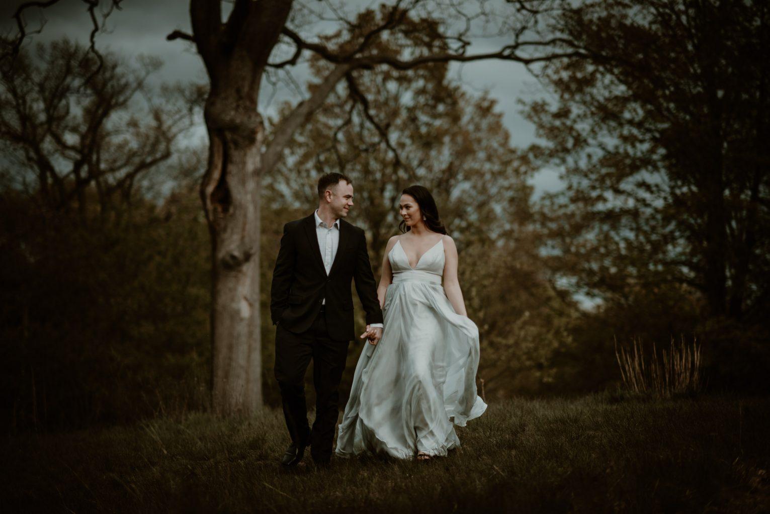 Michigan wedding- bride and groom walking by trees
