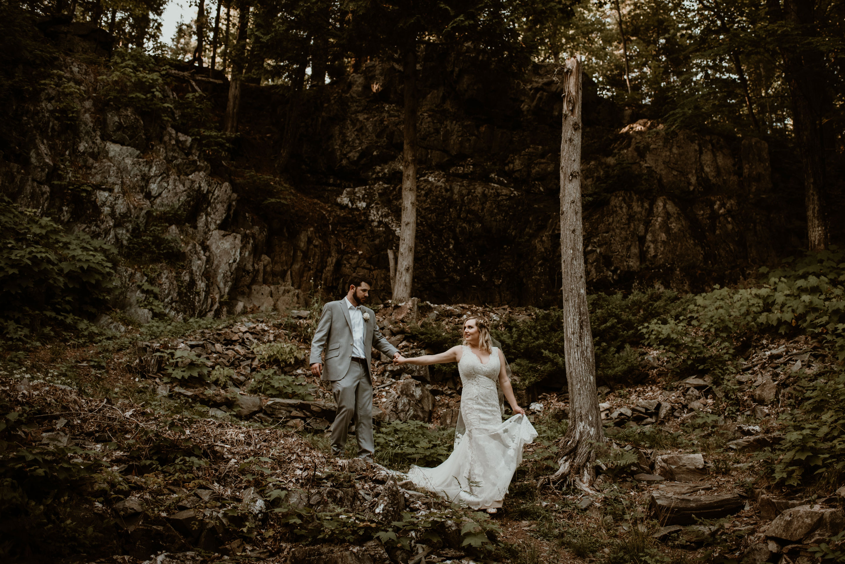 Elopement in Michigan's UP - bride and groom walking up a trail by a cliff.