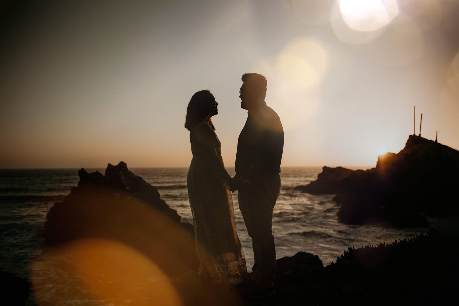 Silhouette of couple eloping in San Francisco by ocean at sunset.