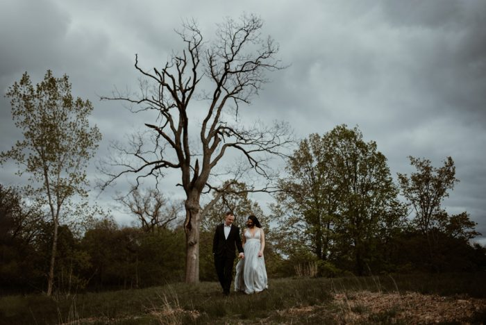 Bride and groom walking together under a big dead tree in Toronto