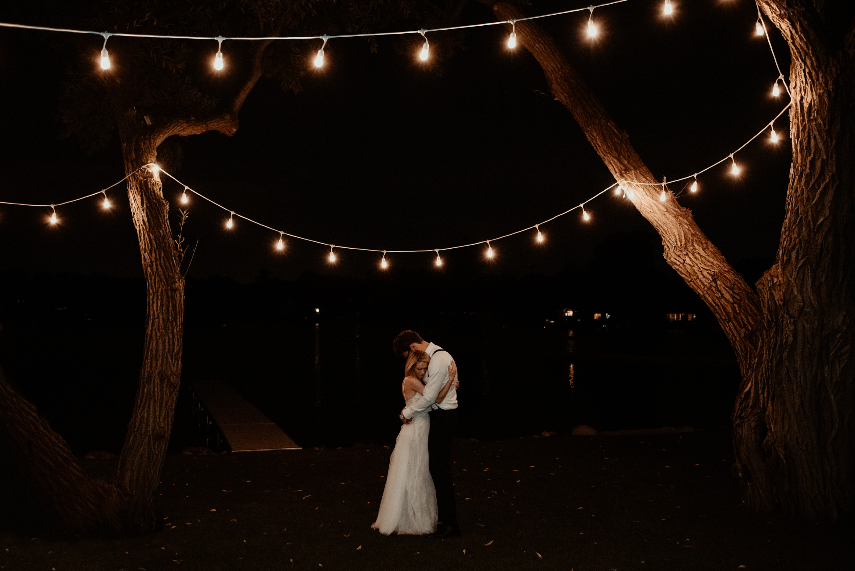 Bride and groom dancing at night under string lights