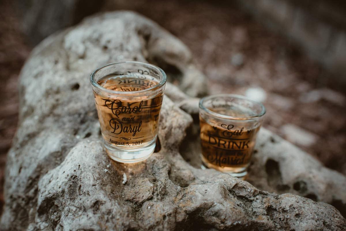 Custom wedding shot glasses on a rock.