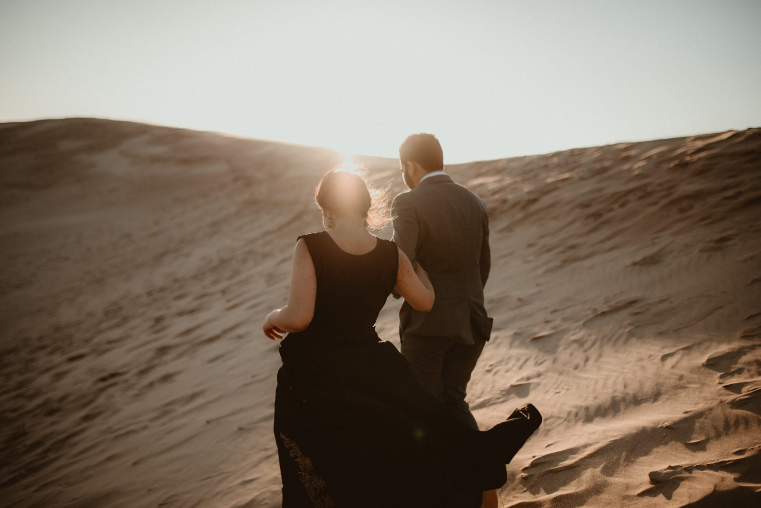 Couple holding hands as they walk across the Silver Lake Sand Dunes, with the sun behind them