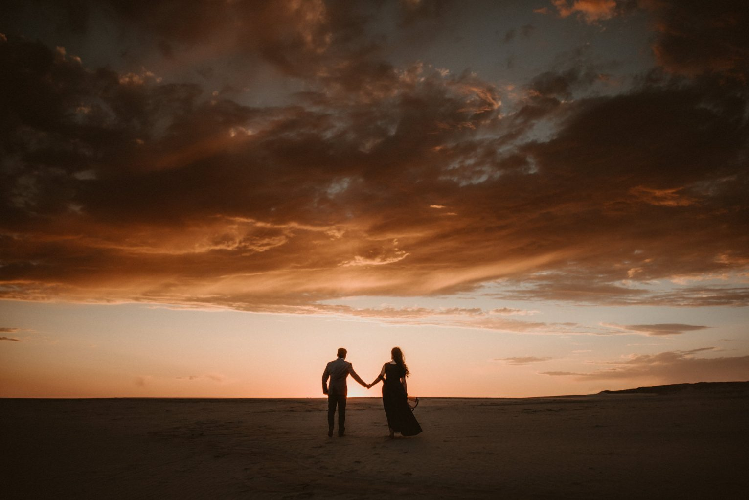 Silhouette of a couple at sunset holding hands as they walk across the Silver Lake Sand Dunes