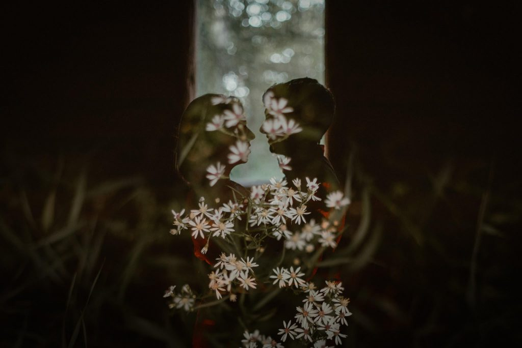 Double exposure with couple and wildflowers.