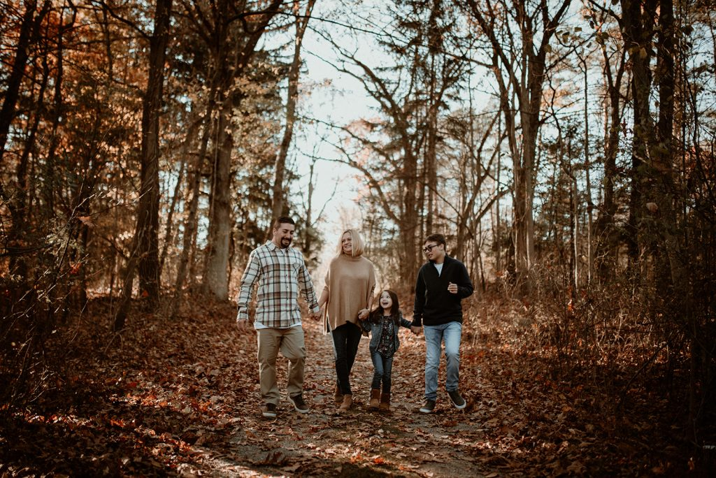 Family walking in the woods in fall