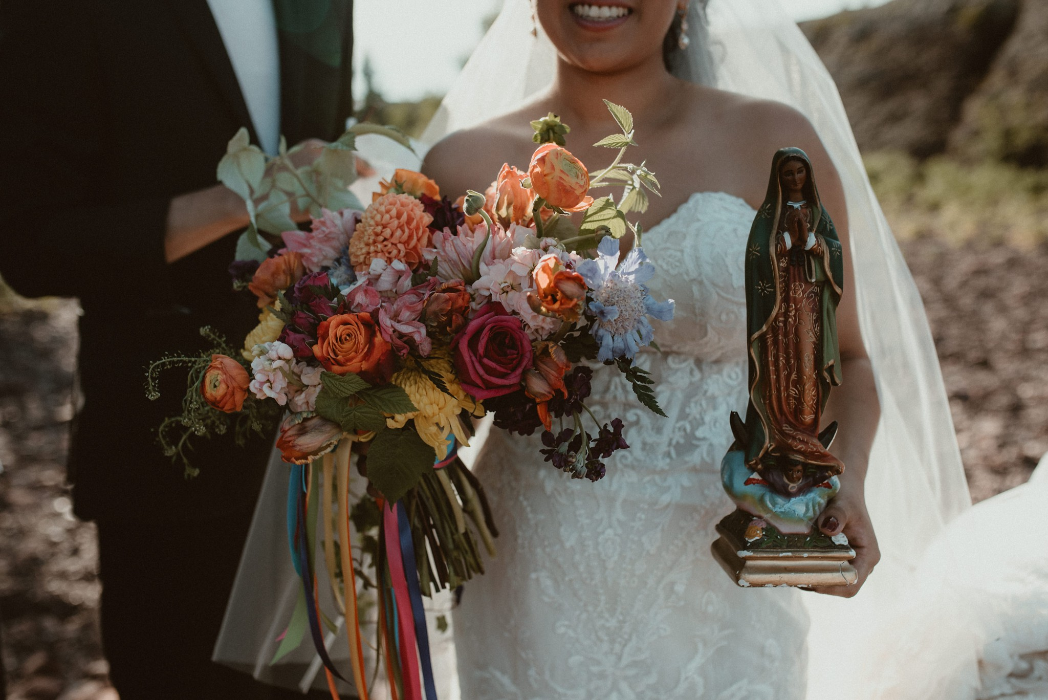 The bride holding her bouquet and a statue of Mary