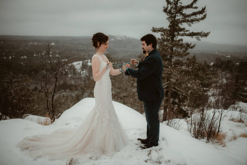 Handfasting ceremony at elopement on Sugarloaf Mountain in Marquette, MI