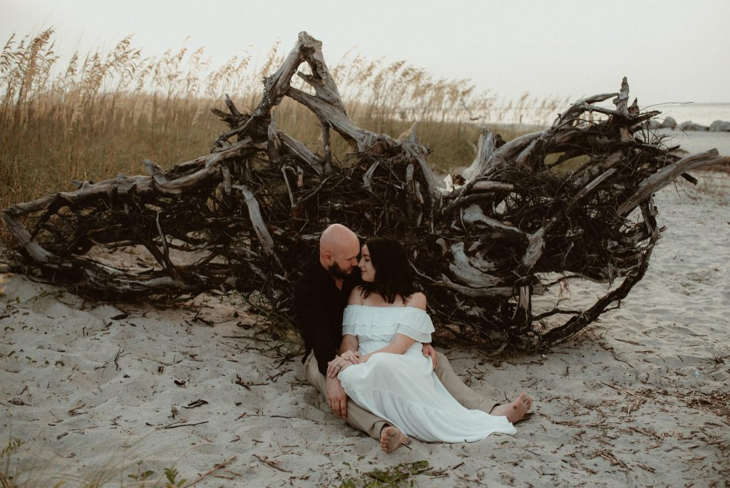 Couple's portrait in the sand by tree roots